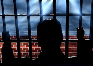 silhouette of a person behind bars